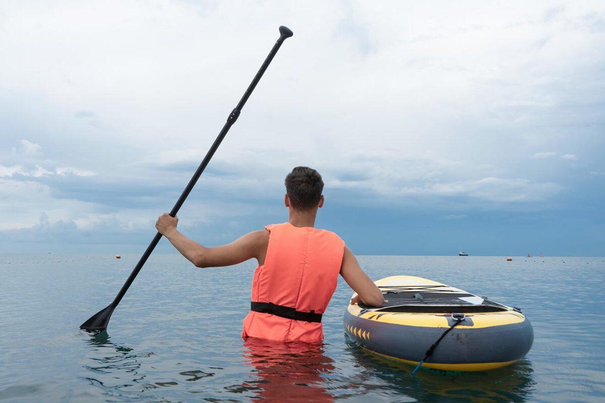 Stand Up Paddler mit Rettungsweste im Wasser